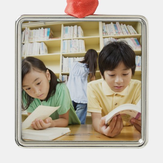 Elementary school students reading a book metal ornament
