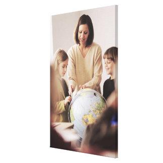 Elementary school teacher showing globe to canvas print