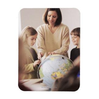 Elementary school teacher showing globe to magnet