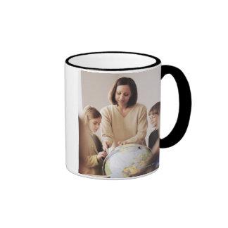 Elementary school teacher showing globe to ringer coffee mug