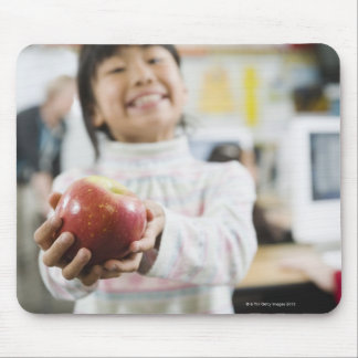 Elementary student holding an apple in her hand mouse pad