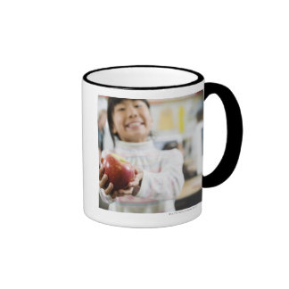 Elementary student holding an apple in her hand coffee mug