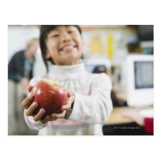 Elementary student holding an apple in her hand postcard