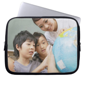 Elementary students and teacher looking at laptop sleeve