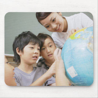 Elementary students and teacher looking at mouse pad