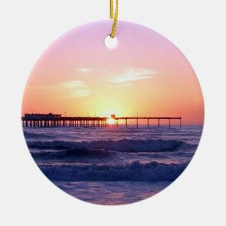 Embarcadero del océano en la puesta del sol adorno navideño redondo de cerámica