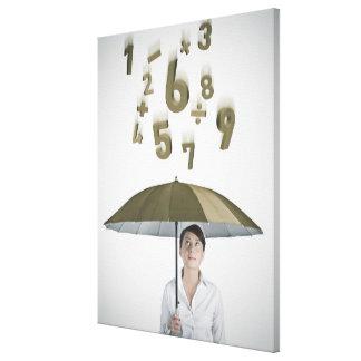 Empresaria debajo del paraguas con números y lienzo envuelto para galerias