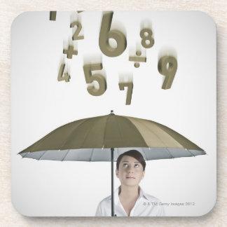 Empresaria debajo del paraguas con números y posavasos