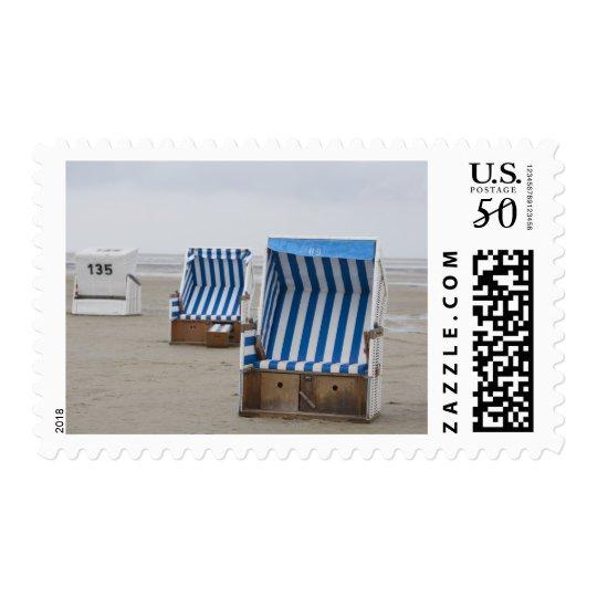 empty beach chairs on beach postage