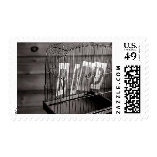 Empty bird cage postage stamp