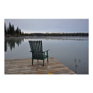 Empty chair on lake deck poster