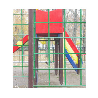 Empty children's playground and a slide notepad