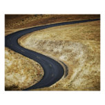 Empty winding paved road posters