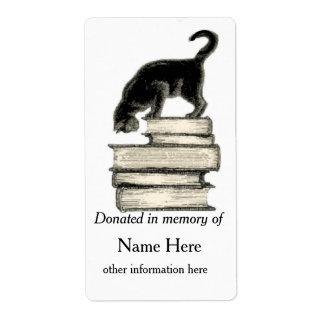 En memoria de gato en la pila de libros del etiqueta de envío