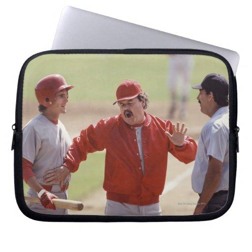 Encargado del béisbol que discute con el árbitro y mangas computadora