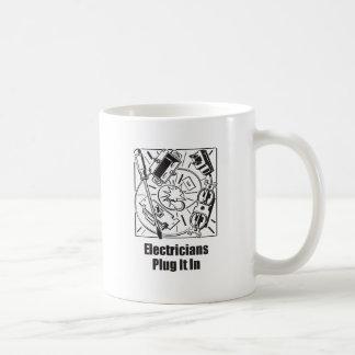 Enchufe de los electricistas él adentro taza de café