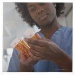 Enfermera de sexo femenino jamaicana que comprueba azulejo cuadrado grande