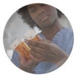 Enfermera de sexo femenino jamaicana que comprueba platos para fiestas