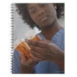Enfermera de sexo femenino jamaicana que comprueba spiral notebook