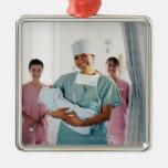 Enfermera del sitio de entrega que detiene al bebé ornamentos de navidad