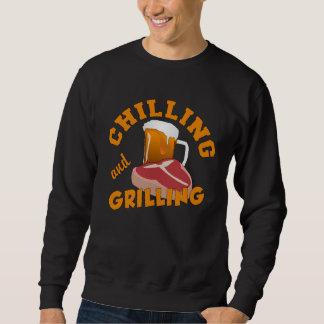 Enfriando y asando a la parrilla el camisetas y sudadera
