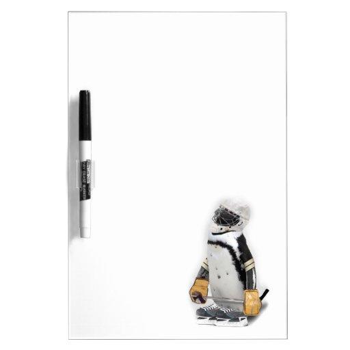 Engranaje del hockey del pequeño pingüino que pizarras blancas