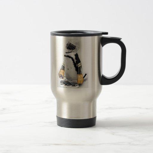 Engranaje del hockey del pequeño pingüino que tazas de café