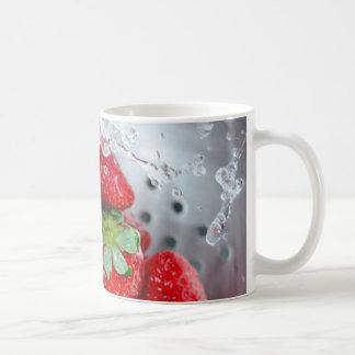 Enjuague de la fresa con agua tazas de café