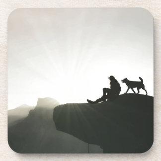 Enlace del hombre y del perro en la montaña posavasos