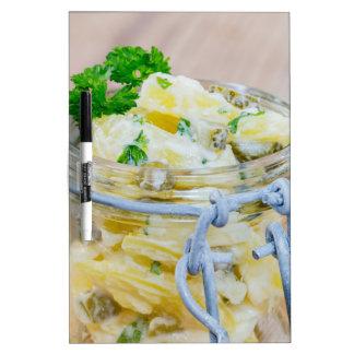 Ensalada de patata en un tarro en de madera tablero blanco