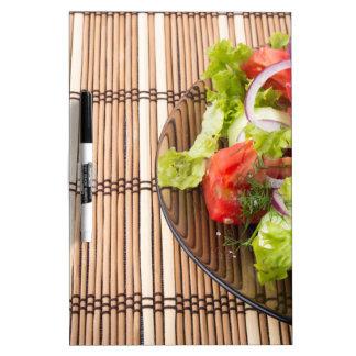 Ensalada vegetariana de verduras frescas en un pizarra blanca
