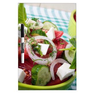 Ensalada vegetariana útil con los tomates crudos pizarras blancas de calidad