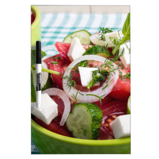 Ensalada vegetariana útil con los tomates crudos tableros blancos