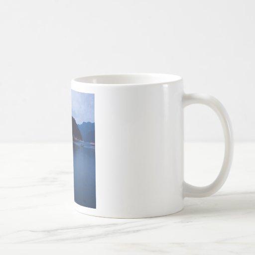 Ensenada profunda de la puesta del sol en la oscur tazas de café