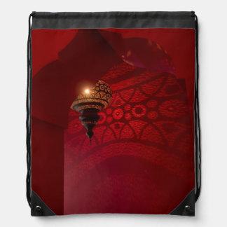 Entrada arqueada y linterna iluminada mochilas