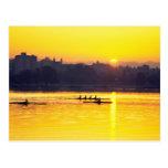Entrenamiento del Rowing en la puesta del sol Postal