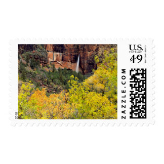 Ephemeral waterfall pours out of slot in cliff postage stamp