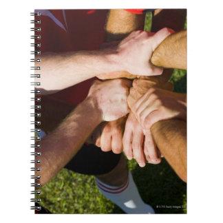 Equipo con brazo-en libro de apuntes