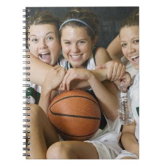 Equipo de baloncesto femenino que sonríe, retrato libros de apuntes