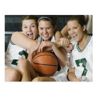 Equipo de baloncesto femenino que sonríe, retrato postal