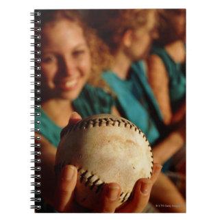 Equipo del softball de los adolescentes que se spiral notebooks
