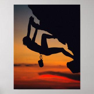 Escalador de roca colgante en la salida del sol póster