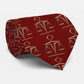 Escalas de cobre amarillo de la justicia en rojo corbata