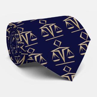 Escalas de oro de la justicia en casi azules corbata