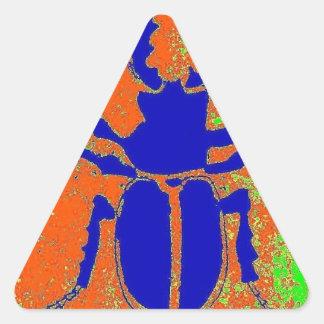 Escarabajo azul en la tierra anaranjada por pegatina triangular