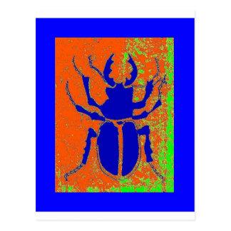 Escarabajo azul en la tierra anaranjada por tarjeta postal