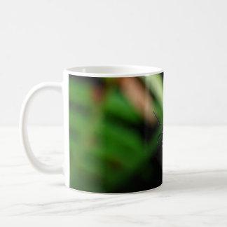 Escarabajo rojo brillante en la hoja verde taza básica blanca