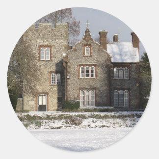 Escena bonita de la nieve con los edificios viejos pegatina redonda