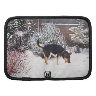 Escena de la nieve del invierno con el perro negro planificadores