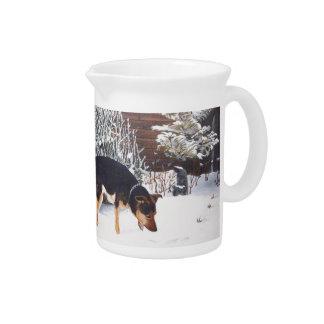 Escena de la nieve del invierno con el perro negro jarras para bebida